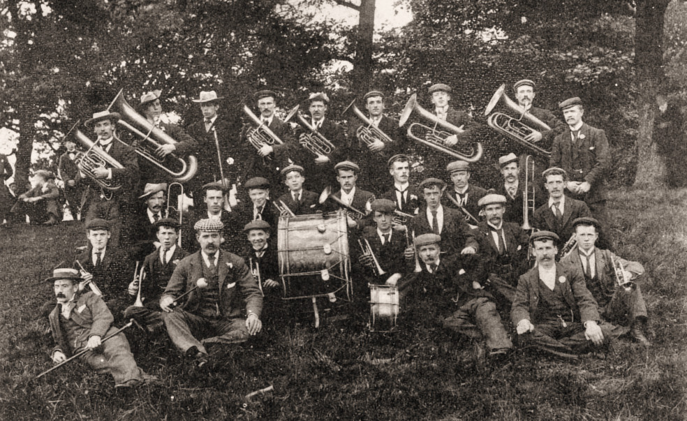 A group of band players holding their brass instruments.